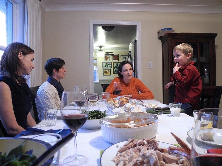 טיפים להורים להרגלי אכילה נכונים לילדים: שלוש נשים וילד יושבים סביב שולחן מלא באוכל