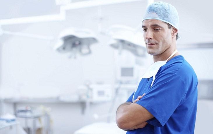 רופא מנתח עומד בחדר ניתוח עם ידיים שלובות