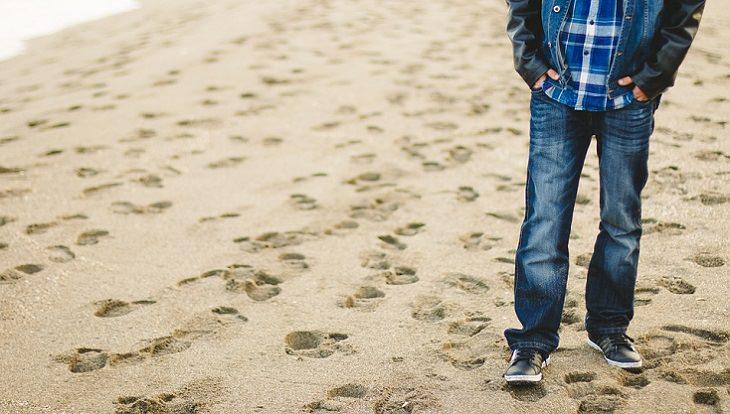 אדם עומד בחוף ים שמלא בטביעות רגליים