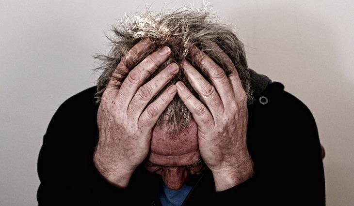 היתרונות הבריאותיים של משקה אננס: אדם מחזיק את ראשו בכפות ידיו