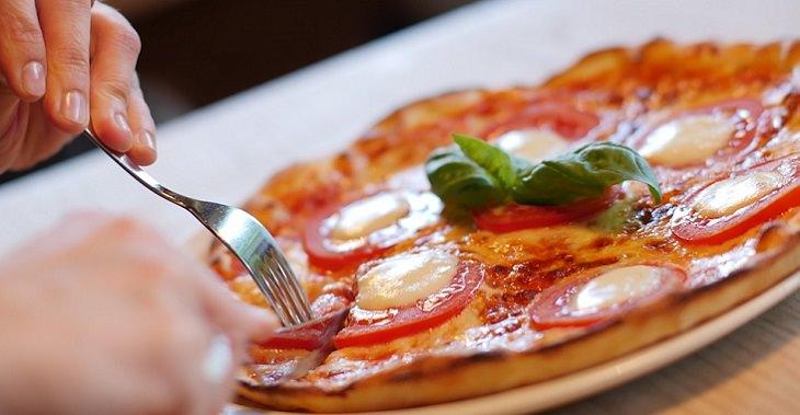 טיפים לשיפור תפקוד מערכת העיכול: יד חותכת פיצה