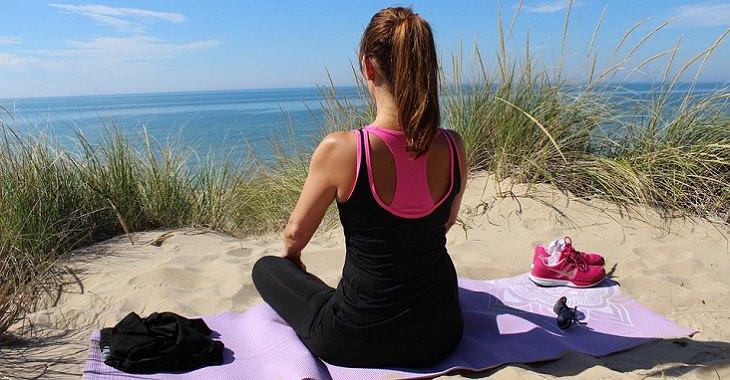 מדיטציית המודעות: אישה עושה מדיטציה על חוף הים