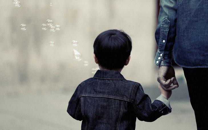 טיפים מדעיים לגידול ילדים מצליחים: ילד מפריח בועות סבון ומחזיק לאימו את היד
