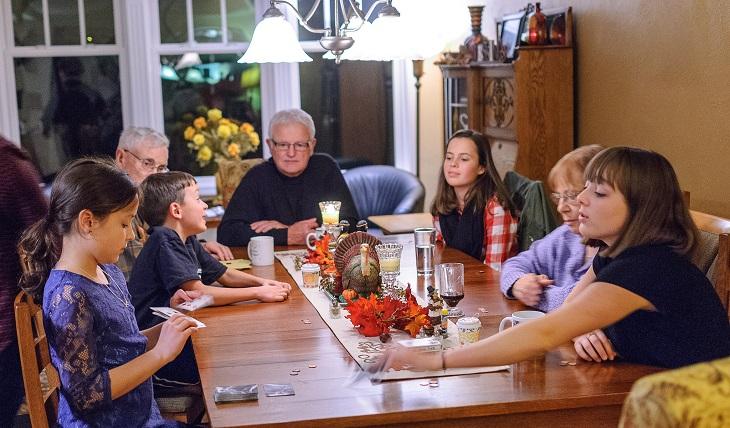 """משחקי לוח להדפסה מאתר """"את זה"""": משפחה משחקת במשחק לוח"""