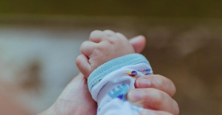 דברים שחשוב לדעת על ימיו הראשונים של תינוק: אישה אוחזת ביד של תינוק