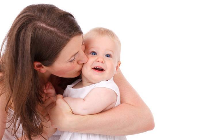 אמא מנשקת תינוקת שמחייכת