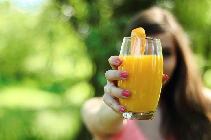 משקאות להורדת כולסטרול: אישה מחזיקה כוס משקה מול המצלמה