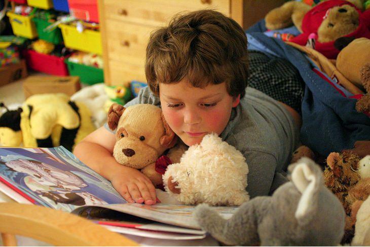 ילד מוקף בבובות קורא ספר