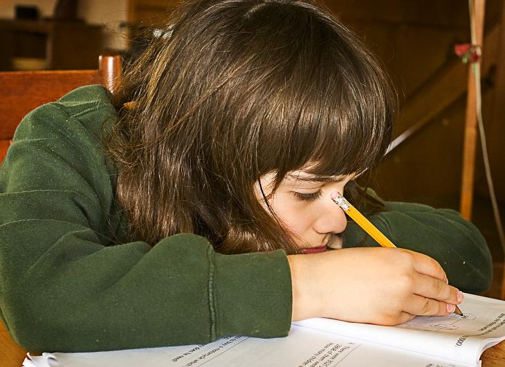 חסרונות של שיעורי בית: ילדה שעושה שיעורי בית בחוסר חשק