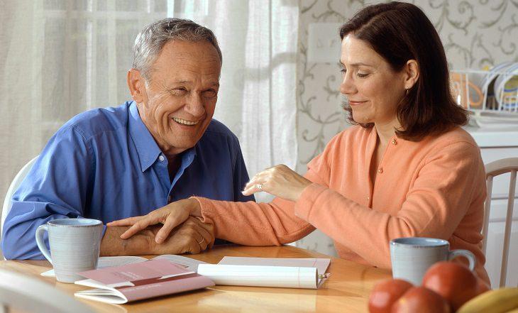 זוג מבוגרים יושבים לצד שולחן במטבח ומחייכים