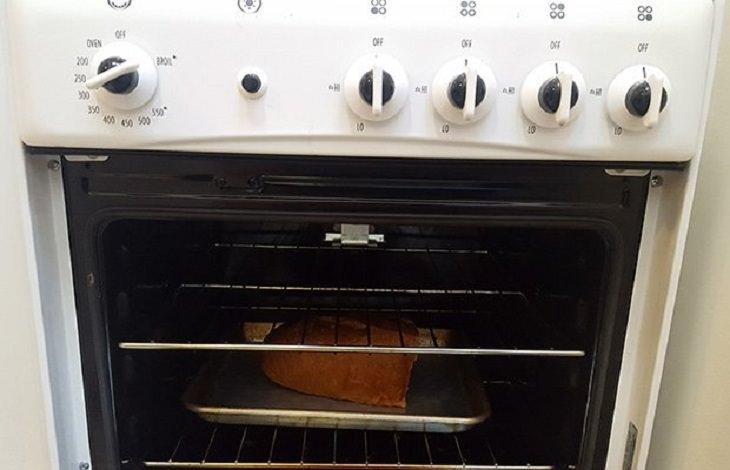 שיטה להפיכת לחם ישן לטרי: כיכר לחם על תבנית בתוך תנור אפייה