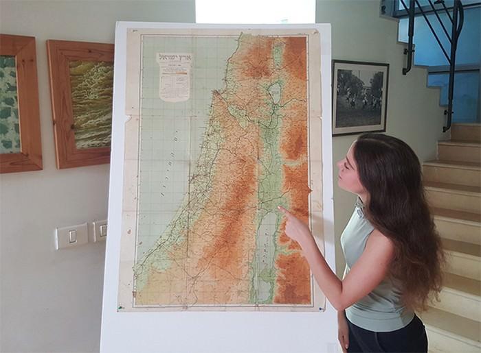 מפת ישראל 1945: אישה עומדת לצד המפה ומצביעה עליה