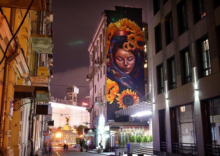 ציור קיר של אישה עם זר פרחים שמקשט את השיער