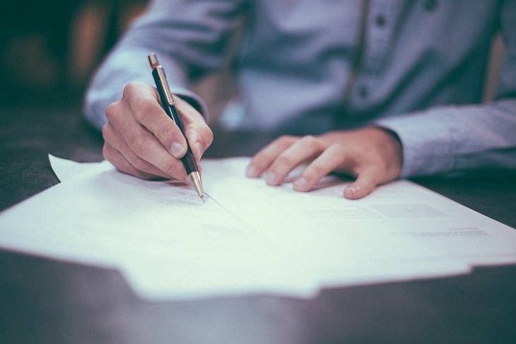 כל מה שצריך לדעת על הכנת צוואה: יד אוחזת בעט וחותמת על מסמך