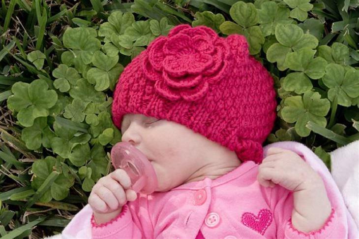 תינוקת עם כובע גרב ישנה על דשא
