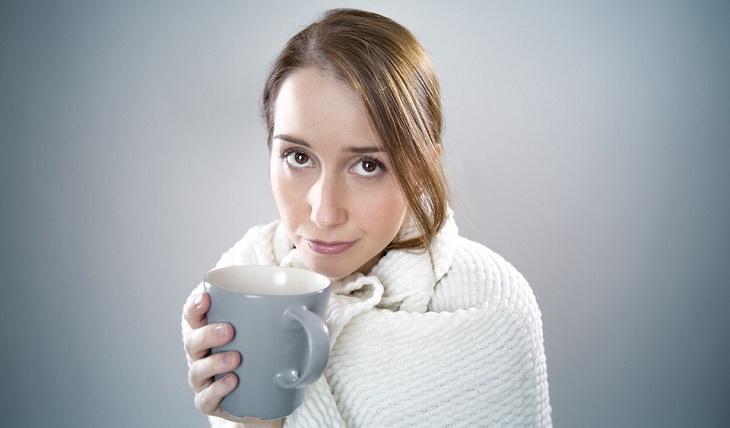אישה חולה מחזיקה כוס תה