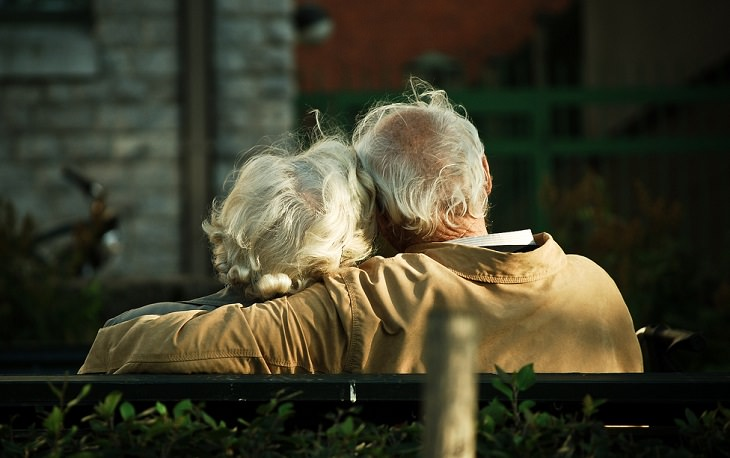 זוג מבוגרים מחובקים על ספסל ומצולמים מהגב