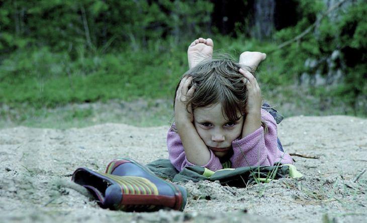 חינוך עדין לילדים: ילדה עם מבט זעוף תופסת את ראשה בתנוחת שכיבה