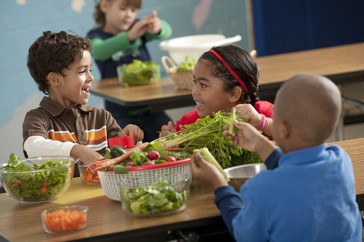 ילדים ממיינים ירקות על שולחן ומחייכים