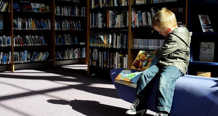 ילד קורא לבד בספרייה
