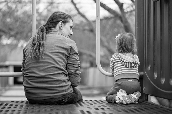 ילדה יושבת ליד אמא שלה