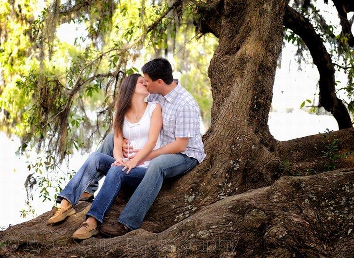 זוג מתנשק על גזע עץ גדול