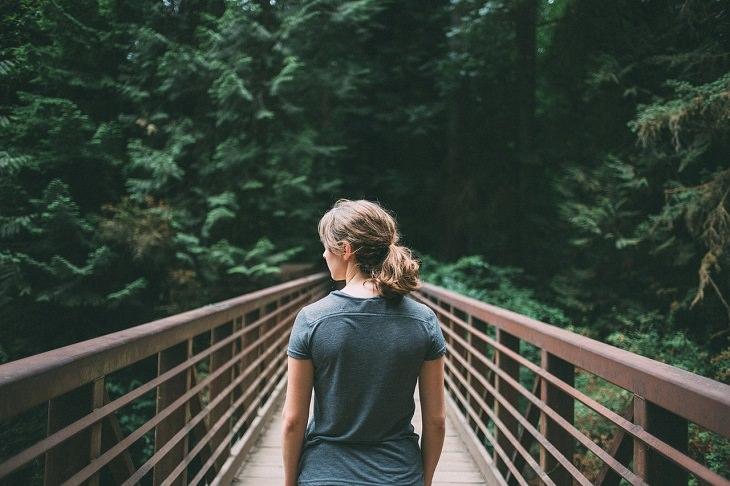 אישה עומד על גשר עם הגב למצלמה