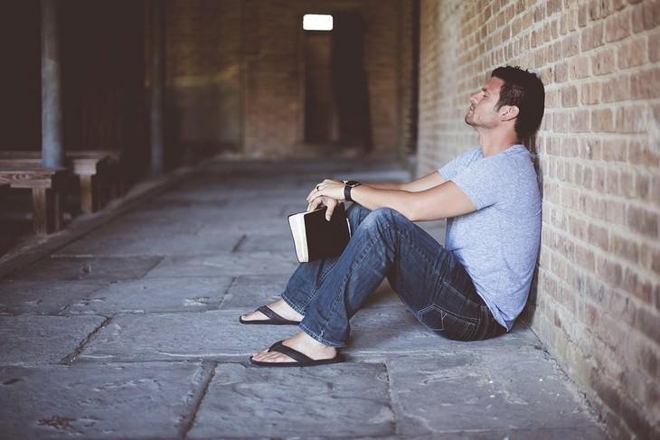 אדם נשען בישיבה על קיר לבנים עם ספר בידו