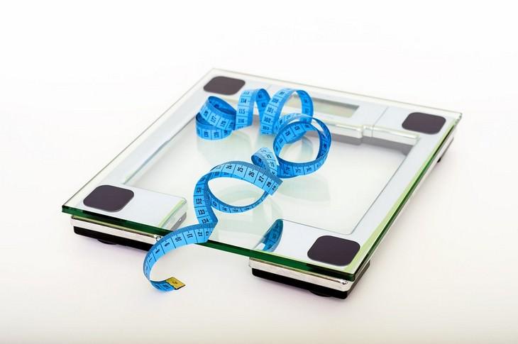 דרכים טבעיות למניעת צרבת: משקל דיגיטלי עם סרט מדידה מונח עליו