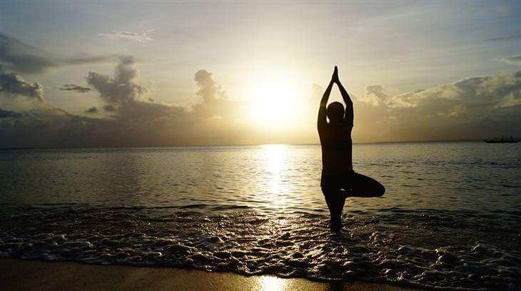 הוכחה לקיומם של ערוצי אנרגיה בגוף: צללית של אדם עושה יוגה על קו המים של חוף ים