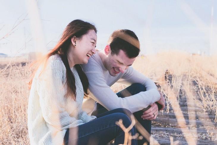 גבר ואישה יושבים מחויכים זה לצד זו בשדה חיטה