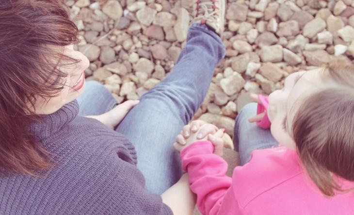 ילדה ואם מחזיקות ידיים על דרך חצץ