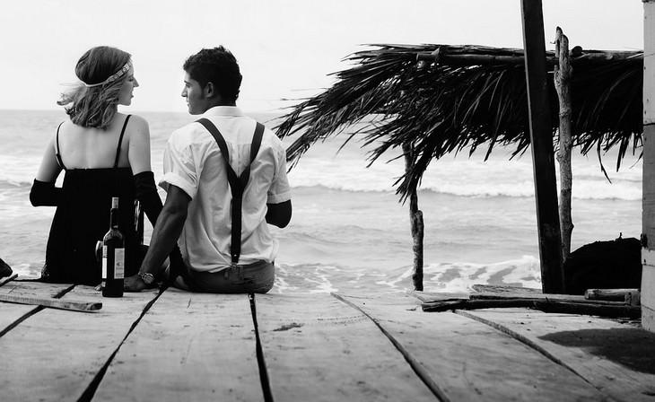 זוג יושב על המזח מול הים
