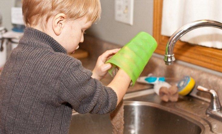 ילד קטן שוטף כוס בכיור