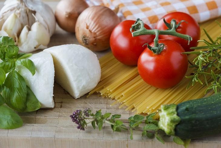 מתכונים צמחוניים: צרור עגבניות, בזיליקום ומוצרלה על קרש חיתוך מעץ