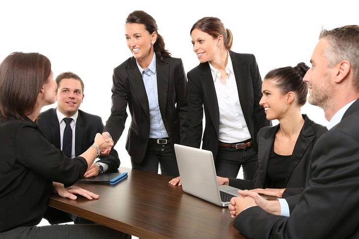 שתי נשים לוחצות ידיים לאנשים בישיבה משרדית