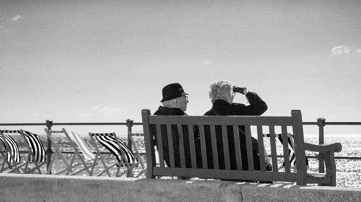 שיר משעשע על גיל הזהב: זוג מבוגר יושב על ספסל ליד הים