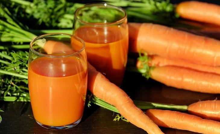 מתכון למשקה בריאות גזר-ג'ינג'ר-לימון: כוס עם מיץ גזר ולידה גזרים שלמים
