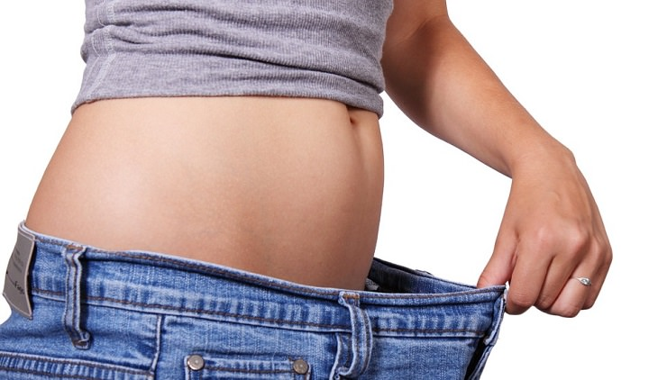 מתכון למשקה בריאות גזר-ג'ינג'ר-לימון: אישה אוחזת בג'ינס שגדול עליה