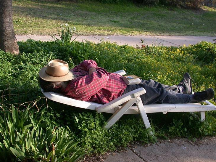 איש שוכב על כיסא שיזוף עם כובע על פניו