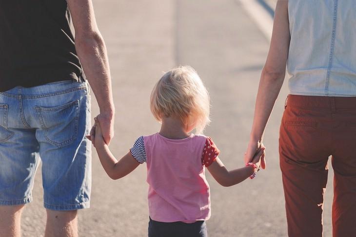 צילום מהגב של ילדה מחזיקה בידיים של שני הוריה