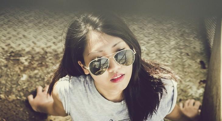 אישה עם משקפיי שמש יושבת תחת קרני שמש