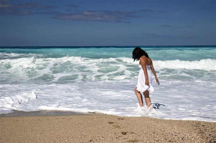 אישה משתכשכת במי הים