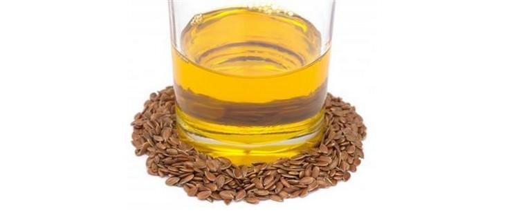 כוס של שמן חרדל עומדת במרכז גרגירי חרדל