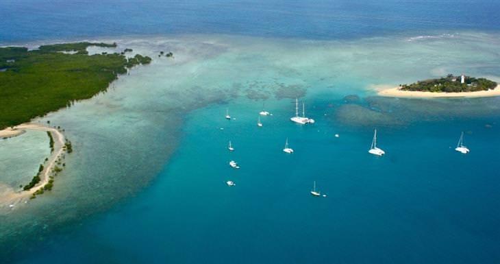 צילום מרחוק של אי קטן בשונית המחסום הגדולה עם סירות סביבו