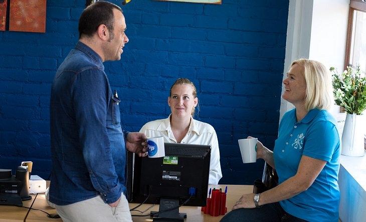 גבר ושתי נשים משוחחים במשרד