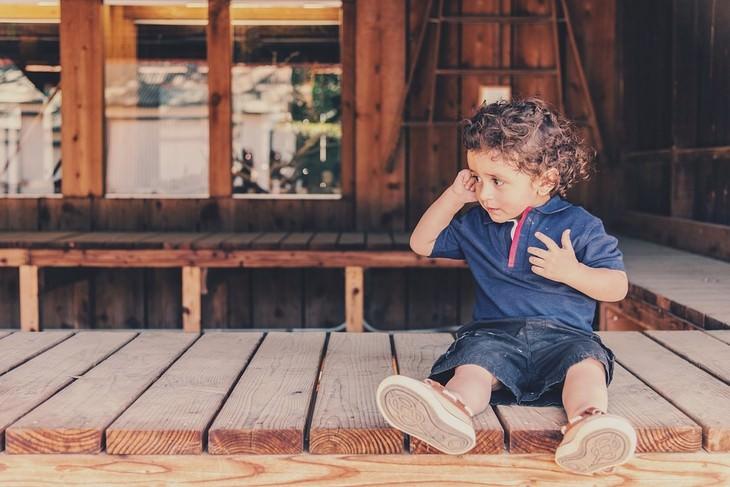 איך לגרום לילדים להקשיב להורים: ילד עם אצבע באוזן יושב על רצפת עץ