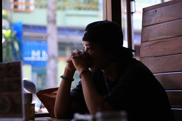 דברים שחשוב לזכור כשאתם חוששים להשמיע את קולכם: גבר יושב במסעדה עם ידיו מול פיו