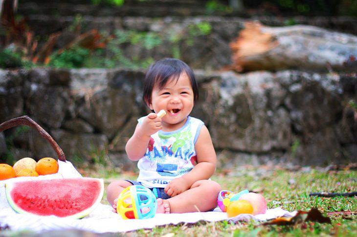 כיצד למנוע השמנת יתר אצל ילדים: ילדה קטנה יושבת על שמיכה ואוכלת