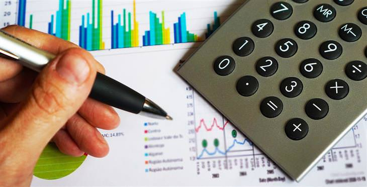 סימולטור לצריכת החשמל: יד של איש עם עט לצד מחשבון, על דפים עם גרפים